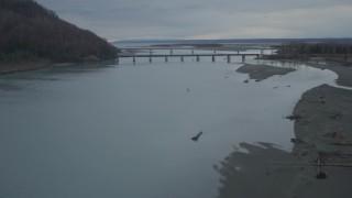 AK0001_0705 - 4K stock footage aerial video flying low over river, approaching Glenn Highway Bridge, winter, Knik River, Alaska