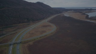 AK0001_0706 - 4K stock footage aerial video fly over wooded hill, Glenn Highway, during winter, Glenn Highway, Alaska