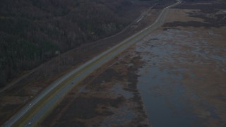 AK0001_0707 - 4K stock footage aerial video following highway by marshlands, forest, during winter, Glenn Highway, Alaska