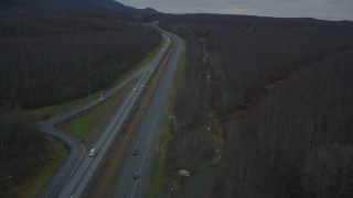 AK0001_0708 - 4K stock footage aerial video following highway through forest during winter, Glenn Highway, Alaska