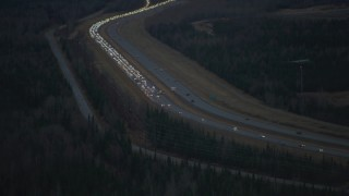 AK0001_0718 - 4K stock footage aerial video approaching accident backing up traffic on Glenn Highway, Alaska, twilight