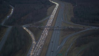 AK0001_0719 - 4K stock footage aerial video flying low over heavy traffic, during winter, on Glenn Highway, Alaska, twilight
