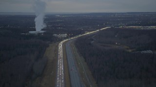 AK0001_0721 - 4K stock footage aerial video flying away from heavy traffic, during winter, on Glenn Highway, Alaska, twilight