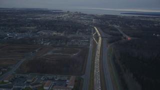 AK0001_0722 - 4K stock footage aerial video following Glenn Highway, winter, revealing Downtown Anchorage, Alaska, twilight
