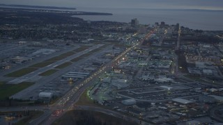 AK0001_0725 - 4K stock footage aerial video flying over large stores by Glenn Highway, revealing Downtown Anchorage, Alaska, twilight