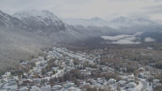 AK0001_0752 - 4K stock footage aerial video snowy residential neighborhood Eagle River Valley, wooded hill, Eagle River, Alaska