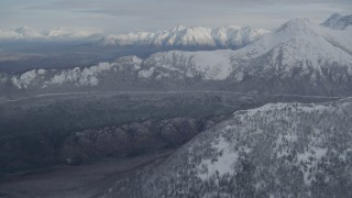 AK0001_0772 - 4K stock footage aerial video approaching wooded valley and snow-capped Chugach Mountains, Alaska