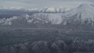 AK0001_0773 - 4K stock footage aerial video tilt up from wooded hill to reveal valley, Chugach Mountains, Alaska