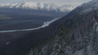 AK0001_0783 - 4K stock footage aerial video fly low over treetops, reveal Knik River Valley, snowy Chugach Mountains, Alaska