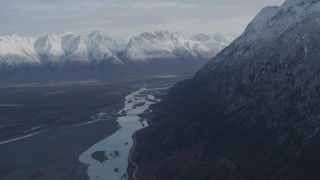 AK0001_0785 - 4K stock footage aerial video tilt from river to reveal Old Glenn Highway, bridge, snowy Chugach Moutains, Knik River Valley, Alaska