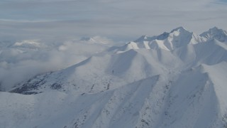 AK0001_0817 - 4K stock footage aerial video clouds, snow-covered Chugach Mountains, Alaska