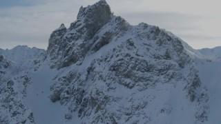 AK0001_0824 - 4K stock footage aerial video ascend snowy slope, approach rocky, snow-covered Chugach Mountains, Alaska