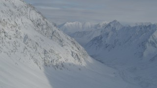 AK0001_0828 - 4K stock footage aerial video flying beside snowy valley, mountain slope, Chugach Mountains, Alaska