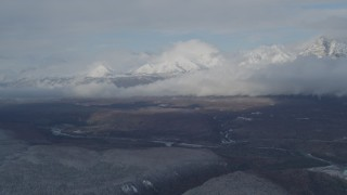 AK0001_0848 - 4K stock footage aerial video flying by Talkeetna Mountains, clouds, and Matanuska River Valley, Alaska in winter
