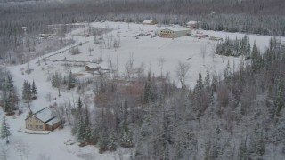 AK0001_0865 - 4K stock footage aerial video orbiting snowy King Ranch, descend to runway, landing, Sutton, Alaska