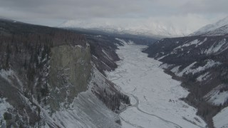 AK0001_0880 - 4K stock footage aerial video approaching tree lined cliff over snowy Matanuska River Valley, Alaska