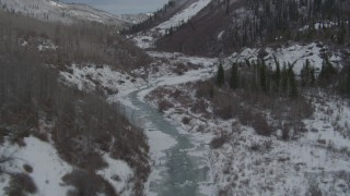 AK0001_0883 - 4K stock footage aerial video flying over snowy gorge and icy river during winter, near Sheep Mountain, Alaska