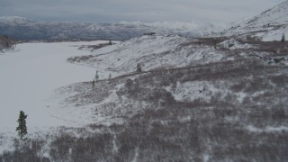 AK0001_0889 - 4K stock footage aerial video fly over snow covered Alaskan Wilderness toward center of Goober Lake, Alaska