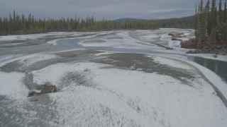 AK0001_0897 - 4K stock footage aerial video flying low over the icy, snow covered river during winter in the Tazlina River Valley, Alaska