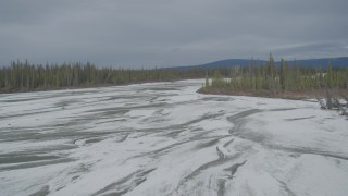 AK0001_0899 - 4K stock footage aerial video flying over frozen, snow covered riverbed during winter, Tazlina River Valley, Alaska