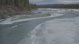 AK0001_0901 - 4K stock footage aerial video flying low over a tree lined, snowy river during winter, Tazlina River Valley, Alaska
