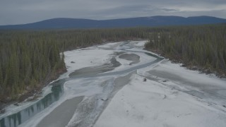 AK0001_0902 - 4K stock footage aerial video fly over icy, snow covered river, ascend to show forest during winter, Tazlina River Valley, Alaska