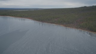 AK0001_0904 - 4K stock footage aerial video flying over icy waters, snow covered forest, during winter, Twin Lakes,  Alaska
