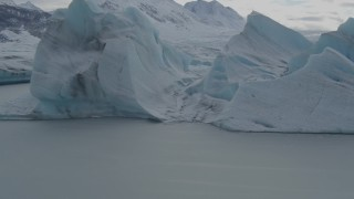 AK0001_0918 - 4K stock footage aerial video flying over glacial ice, revealing snow covered Tazlina Glacier during winter, Tazlina Lake, Alaska
