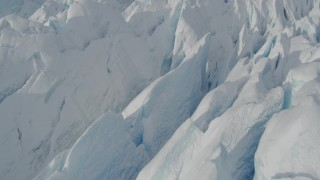 AK0001_0931 - 4K stock footage aerial video flying over snow covered surface of the Tazlina Glacier, tilt to a bird's eye view, Alaska
