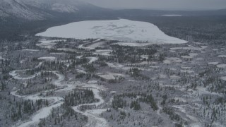AK0001_0955 - 4K stock footage aerial video flying by icy rivers and snow covered ground, during winter, revealing Kaina Lake, Alaska