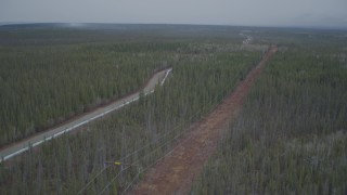 AK0001_0975 - 4K stock footage aerial video approaching power lines during winter, revealing Trans-Alaska Pipeline, Alaska