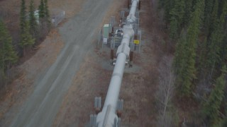 AK0001_0978 - 4K stock footage aerial video following pipeline through forest, during winter, Trans-Alaska Pipeline, Alaska
