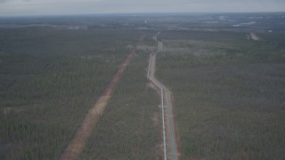 AK0001_0985 - 4K stock footage aerial video follow pipeline, descend towards forest, during winter, Trans-Alaska Pipeline, Alaska