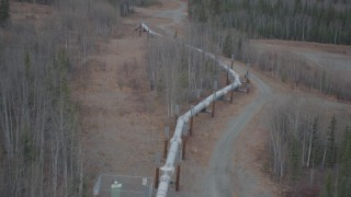 AK0001_0989 - 4K stock footage aerial video follow pipeline as it enters the ground, during winter, Trans-Alaska Pipeline, Alaska