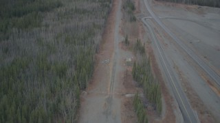 AK0001_0990 - 4K stock footage aerial video fly between forest and road during winter, revealing Trans-Alaska Pipeline, Alaska