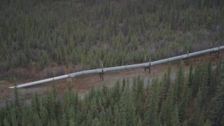 AK0001_0991 - 4K stock footage aerial video approach and orbit pipeline emerging from ground, winter, Trans-Alaska Pipeline, Alaska