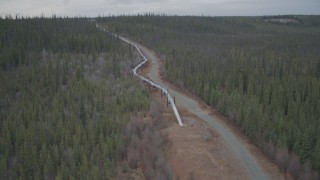 AK0001_0992 - 4K stock footage aerial video orbiting pipeline emerging from ground, winter, Trans-Alaska Pipeline, Alaska