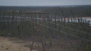 AK0001_1001 - 4K stock footage aerial video follow pipeline past power lines and ponds during winter, Trans-Alaska Pipeline, Alaska