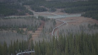 AK0001_1008 - 4K stock footage aerial video approaching pipeline spanning Tazlina River, winter, Trans-Alaska Pipeline, Alaska