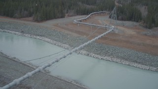 AK0001_1009 - 4K stock footage aerial video follow pipeline spanning Tazlina River during winter, Trans-Alaska Pipeline, Alaska