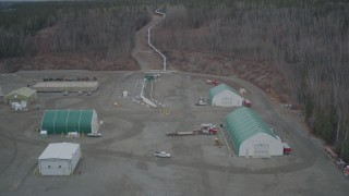AK0001_1010 - 4K stock footage aerial video fly over buildings pipeline rising from ground, winter, Trans-Alaska Pipeline, Alaska