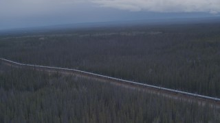 AK0001_1013 - 4K stock footage aerial video flying over a snow covered lake and forest revealing Trans-Alaska Pipeline, Alaska