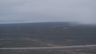 AK0001_1019 - 4K stock footage aerial video flying by forest during a rain storm to reveal a highway in the Alaskan Wilderness