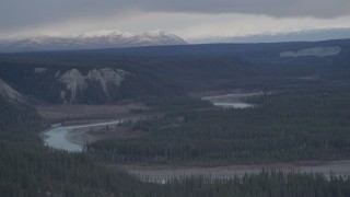 AK0001_1024 - 4K stock footage aerial video the Tazlina River at bottom of forested gorge, snowy mountains in the background, Alaska