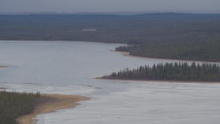 AK0001_1032 - 4K stock footage aerial video flying by ice covered Sucker Lake surrounded by forest, Alaska