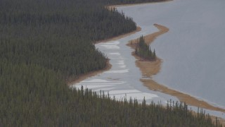 AK0001_1033 - 4K stock footage aerial video forest and an island on snow covered shore of Sucker Lake, Alaska