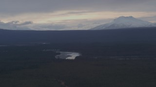 AK0001_1045 - 4K stock footage aerial video flying over forest toward the Tazlina River and snow capped mountains, Alaska