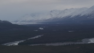 AK0001_1046 - 4K stock footage aerial video flying alongside Tazlina River, forest and snow capped mountains, Alaska