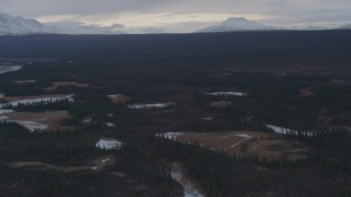 AK0001_1047 - 4K stock footage aerial video flying over icy ponds in an evergreen forest, Alaskan Wilderness