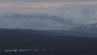 AK0001_1049 - 4K stock footage aerial video wooded hills near lake, snow capped Chugach Mountains, Alaskan Wilderness